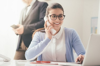 Efficient Smiling Secretary Answering Phone Calls And Talking With Customers, She Is Sitting At Desk And Working With A Laptop